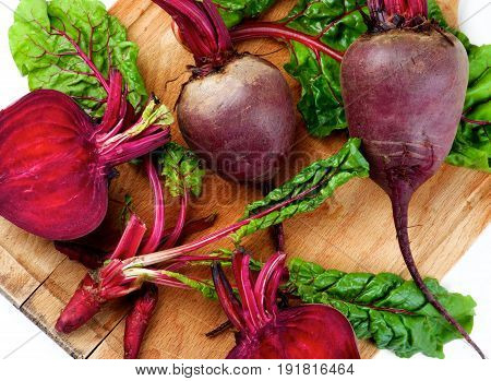 Arrangement of Fresh Raw Organic Beet Roots Full Body Halves and Young Sprouts with Green Beet Tops closeup on Wooden Cutting Board. Top View