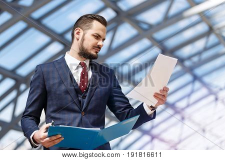 Portrait of mature businessman holding binder and documents over modern building interior background