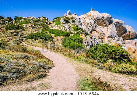 Walky path between bizarre granite rock formations in Capo Testa, Sardinia, Italy.