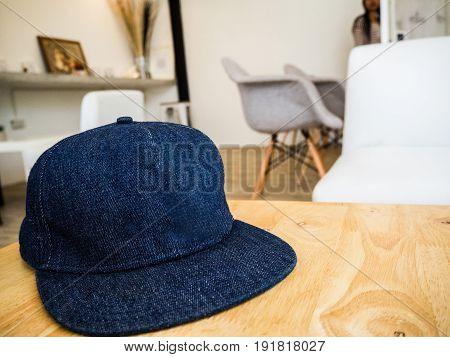 Blue Baseball cap on the table at coffee shop.Baseball cap empty mock up.