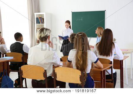 Schoolgirl answering at blackboard in classroom