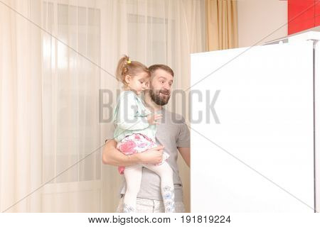 Young man with daughter on arms opening fridge at kitchen