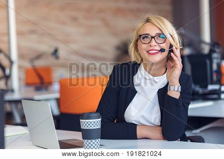 Customer service representative at work. Beautiful young woman in headset working at the computer and smiling while sitting at her working place in office.