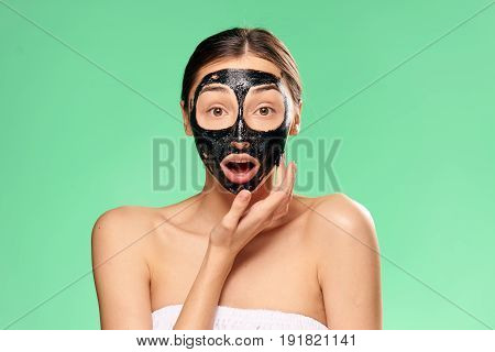 Woman in cosmetic mask, woman on green background.