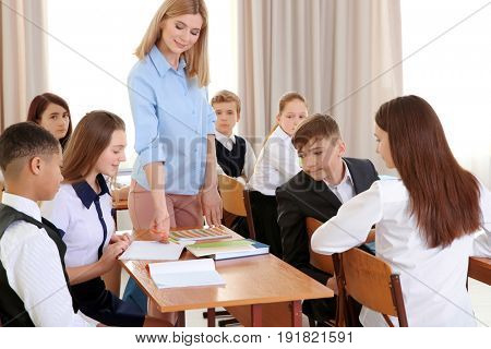 Female teacher and pupils doing task in classroom