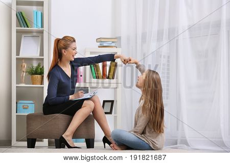 Professional psychotherapist talking with young girl indoors