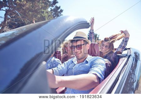 leisure, road trip, travel and people concept - happy friends driving in cabriolet car along country road.