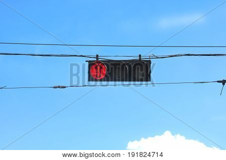 Street traffic signal with red signal and arrow on cloudy sky background
