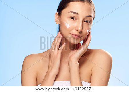 Woman with cream on face, woman with well-groomed face, woman on blue background portrait.