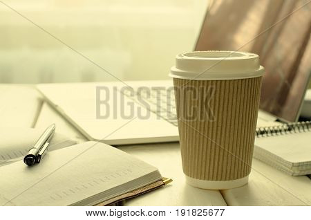 Paper cup of coffee on work-table with office stuff, notepad, laptop, pen and coffee cup, copy space, horizontal, toned