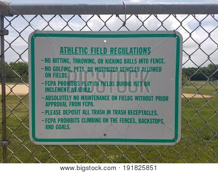 athletic field rules sign on metal chain link fence