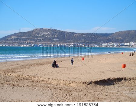 AGADIR, MOROCCO / AFRICA on FEBRUARY 2016: Tourists on beach in travel city landscape with clear blue sky in warm  sunny winter day. Three Arabic words on northwest of Mount Agadir, means: God, King and Nation.