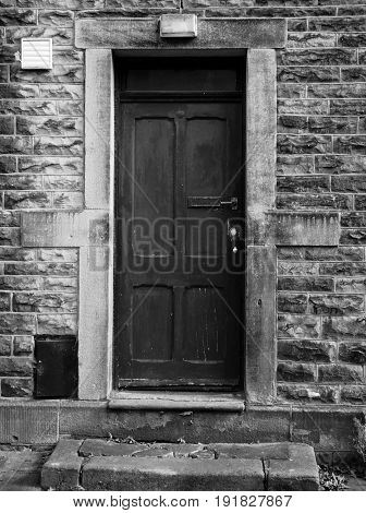 old black door with faded and dented paintwork in a stone wall and frame with raised doorstep