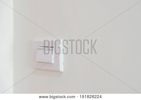 Switch on the wall to turn on the electricity to illuminate the room.