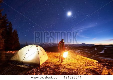 Male Tourist Have A Rest In His Camp At Night, Standing Near Campfire And Tent Under Beautiful Night