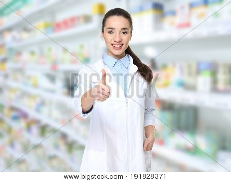 Young female pharmacist at work. Blurred shelves with pharmaceutical products on background