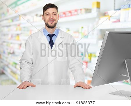 Male pharmacist near counter with computer at work. Blurred shelves with pharmaceutical products on background