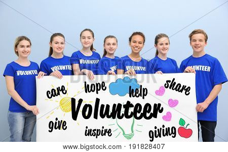 Group of teens holding poster with word VOLUNTEER on color background