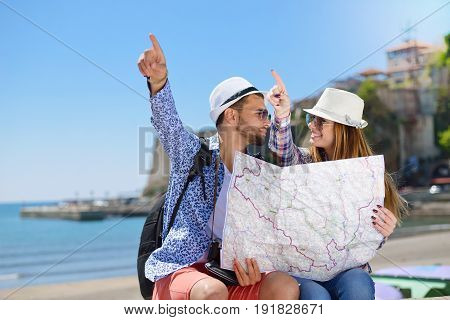 summer holidays, dating and tourism concept - smiling couple in sunglasses with map in the city.