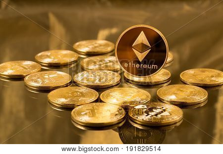 Single ether or ethereum coin over bitcoins on gold background to illustrate blockchain and cyber currency