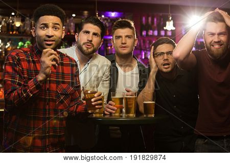 Upset male friends watching sport game or football match and drinking beer at bar or pub