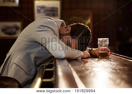 Young drunk man sleeping on a pub counter