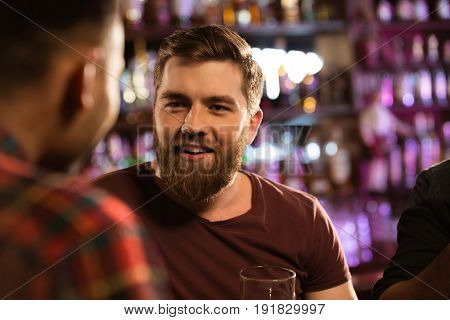 Close up of a two happy male friends drinking draft beer at bar or pub