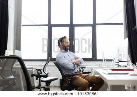 Mature business man sitting on a chair with arms folded and looking at computer screen at the office