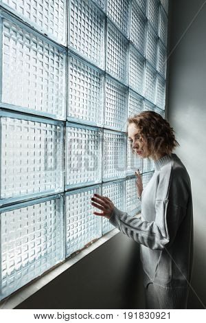 Side view of girl with curly hair looking in window seriously
