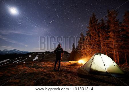 Male Tourist Have A Rest In His Camp Near The Forest At Night. Man Standing Near Campfire And Tent U