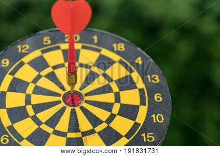 Business goal or target concept with a red dart in the center of dartboard.