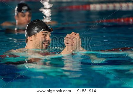 Close up of happy male swimmer shaking another swimmers hand in a swimming pool