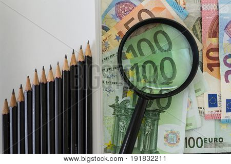 Magnifying glass on pile of Euro banknotes and pencils as rising graph as business financial tax concept.