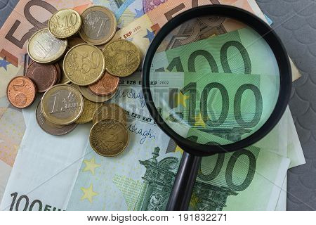 Magnifying glass on pile of Euro banknotes and coins as business financial tax concept.
