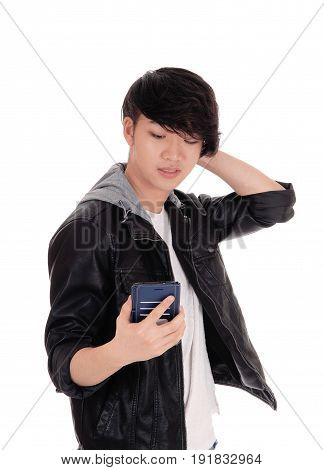 A surprised Asian man looking at his cell phone and is wondering what he is seeing at his phone isolated for white background.