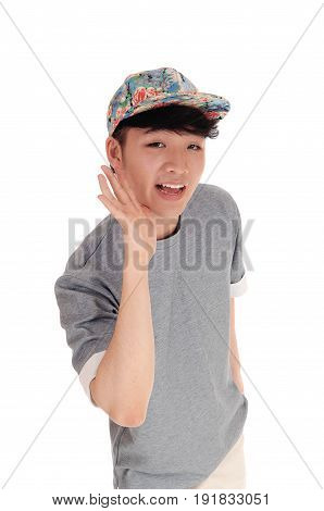 A happy Asian teenager in a closeup image holding his hand on his face wearing a cap on his head isolated for white background.