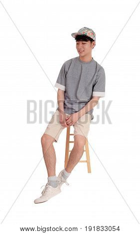 A young Asian teenager sitting on a chair in shorts and a cap smiling isolated for white background.