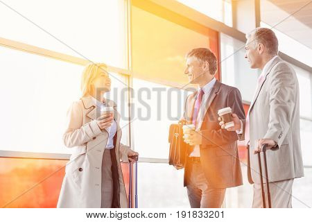 Businesspeople with coffee cups talking on railroad platform