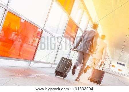 Rear view of middle aged businessmen with luggage rushing on railroad platform