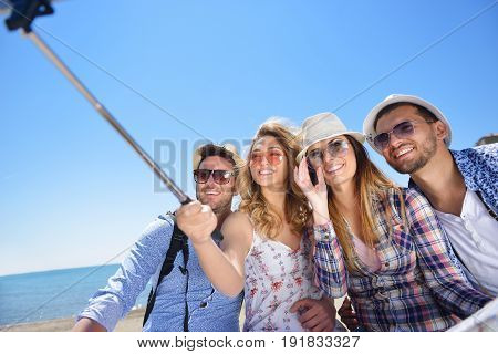 tourism, travel, people, leisure and technology concept - group of smiling teenage friends taking selfie with smartphone and monopod at the city.