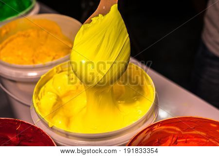 scoop the yellow ink out the barrel . the screen printing tee shirt factory always use plastisol ink for print on any fabric