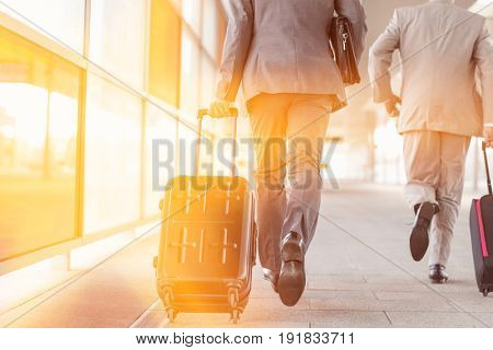 Rear view of businessmen with luggage running on railroad platform