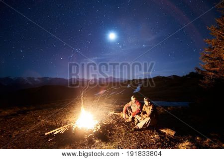 Two Male Tourists Have A Rest In His Camp Near The Forest At Night. Guys Sitting Near Campfire And T