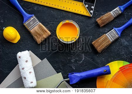 decorating and house renovation tools and accessories on black stone table background top view.