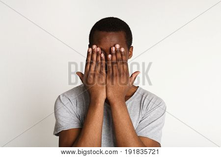 See no evil concept. Portrait of young scared black man covering eyes with hands while standing against white studio background. Confused guy close eyes with palms ignoring something