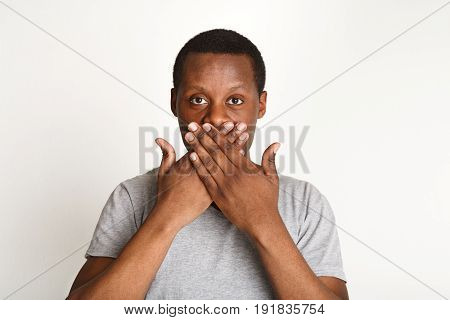 Keep silence. Black man covering mouth with both hands against white studio background, copy space