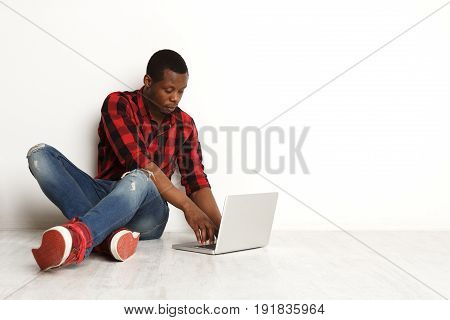 Freelance work with laptop. Blogging male. Concentrated freelancer african-american boy surf internet at white studio background with crossed legs