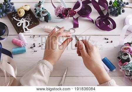 Master making handmade jewelry. Needlewoman workplace with plastic beads, flowers and tools for creating accessories