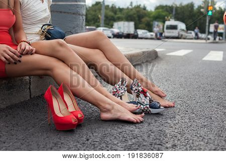 Young girls on roadside, without shoes waiting for car
