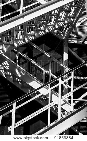 Abstract fragment of metal stairs. Distinctive contemporary composition with geometric structure in black and white.